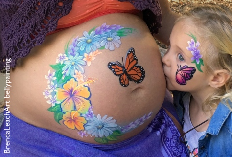little girl kissing her mama's pregnant baby bump, with butterfly bellypainting and face painting