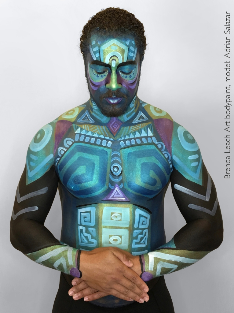 Aztec-inspired bodypaint art on man's torso and face